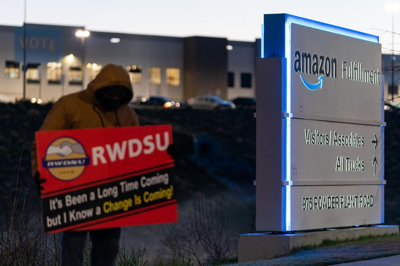 An RWDSU union rep holds a sign outside the Amazon fulfillment warehouse in Bessemer.