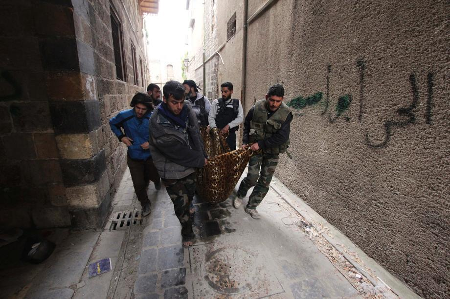 Free Syrian Army fighters carry Joseph, a 19-year-old fighter of the Aoun-bi-allah Brigade which operates under the Free Syrian Army, in a blanket after a sniper shot him in his abdomen in Aleppo on March 16, 2013.