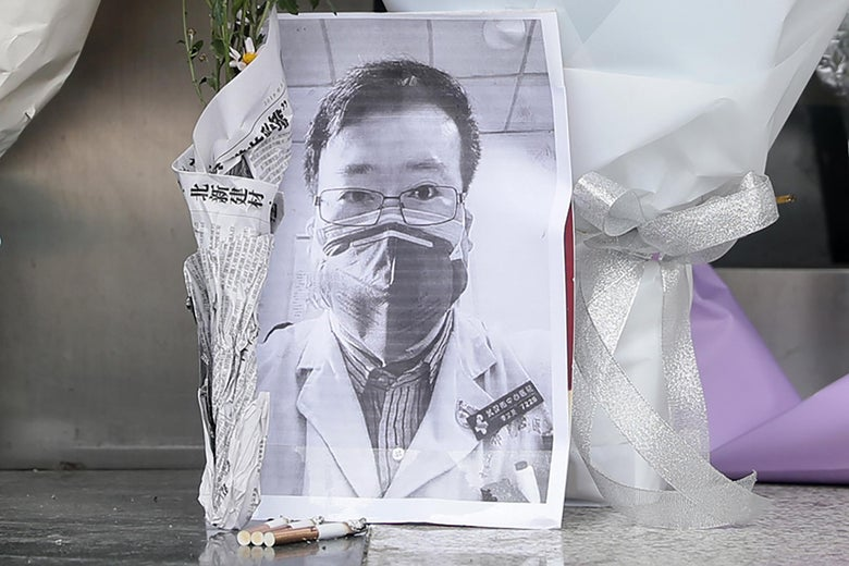 A photo of Li Wenliang is seen surrounded by flower bouquets and used cigarettes.