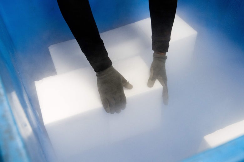 Gloved hands reach inside a cooler to place blocks of dry ice