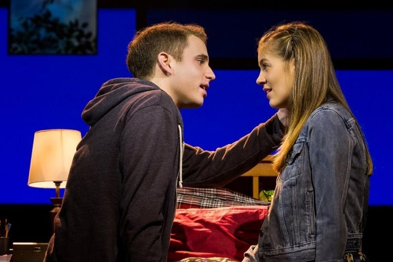 A young man leans toward a young woman on a stage.