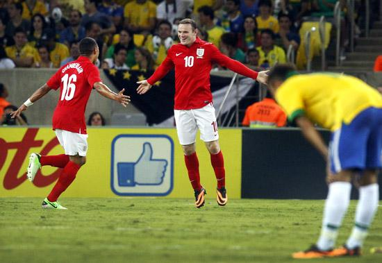England's Wayne Rooney (C) celebrates his goal with teammate Alex Oxlade-Chamberlain, in front of Brazil's Neymar during their international friendly soccer match at the Maracana Stadium in Rio de Janeiro.
