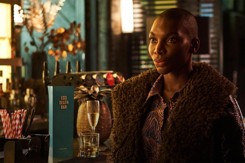 Black woman in a coat looking upset in front of a bar.