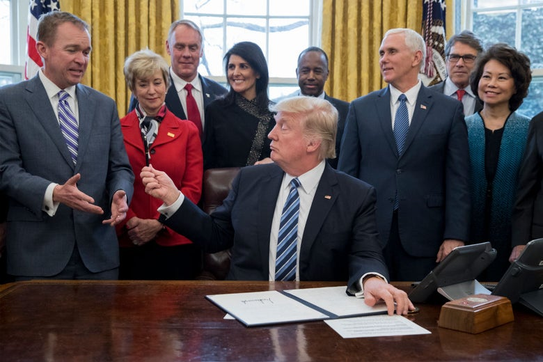 Donald Trump, seated at a desk, hands a pen to Mulvaney as other members of the Cabinet gathered behind Trump laugh.