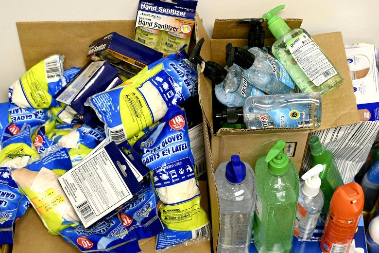 An assortment of cleaning supplies bursting from cardboard boxes.