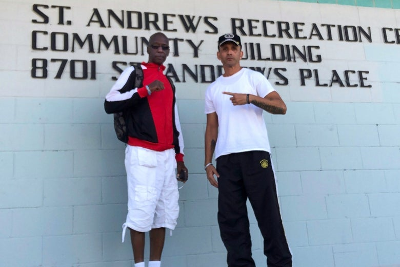 Two men stand in front of a sign that says St. Andrews Recreation Center Community Building.