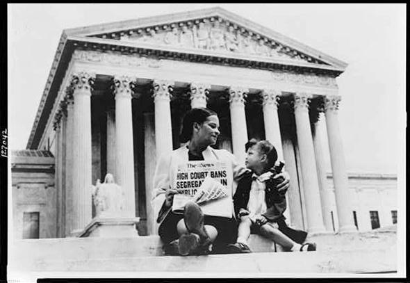 Nettie Hunt, sitting on the steps of the U.S. Supreme Court in Washington, D.C., explains the significance of the Court's May 17th, 1954 desegregation ruling to her daughter Nikie, 3, in Nov. 1954.