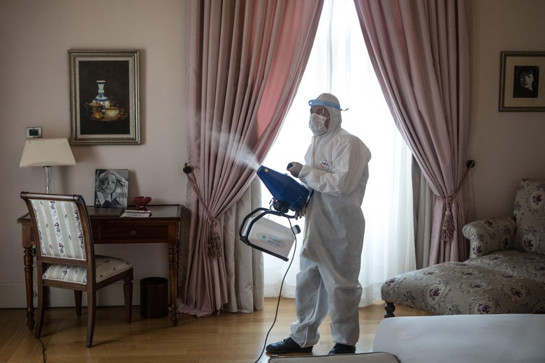 A worker in full PPE sprays disinfectant in a hotel room