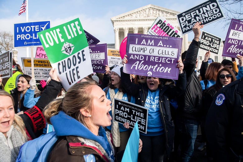 Anti-abortion protesters yell and hold up signs in front of the Supreme Court building.