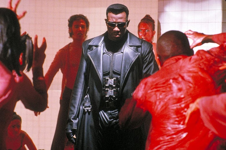 Wesley Snipes in a black leather trench coat is surrounded by red-clad figures.