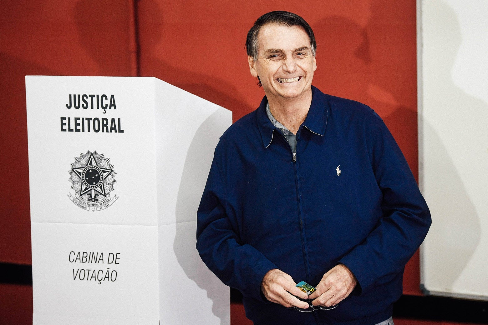 Bolsonaro standing next to a podium, grinning after casting his vote in the general election on Oct. 7.