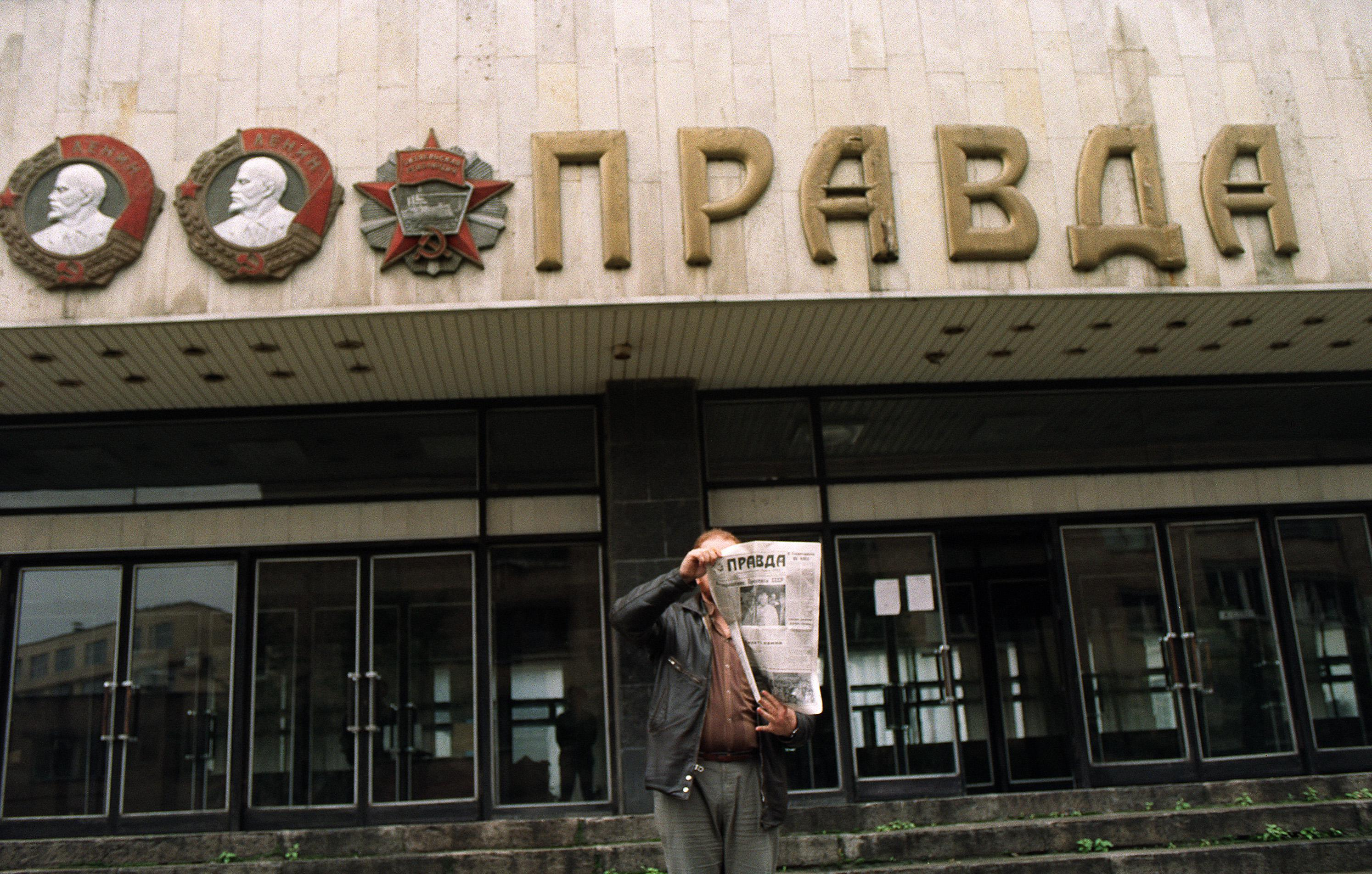 A man shows the headline of the 'Pravda' in front of the entrance of the building of the Soviet newspaper in Moscow on August 28, 1991.