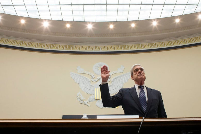 Robert Mueller, pictured against a wall emblazoned with the United States seal, holds up his right hand.
