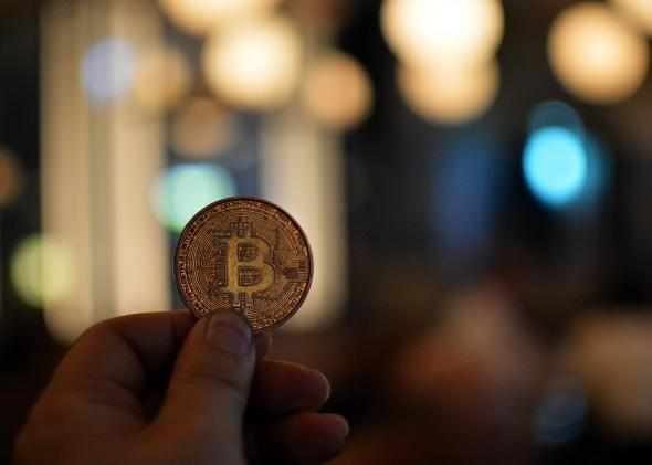A person holds a bitcoin.