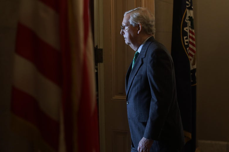 Mitch McConnell walks in a room with an American flag.