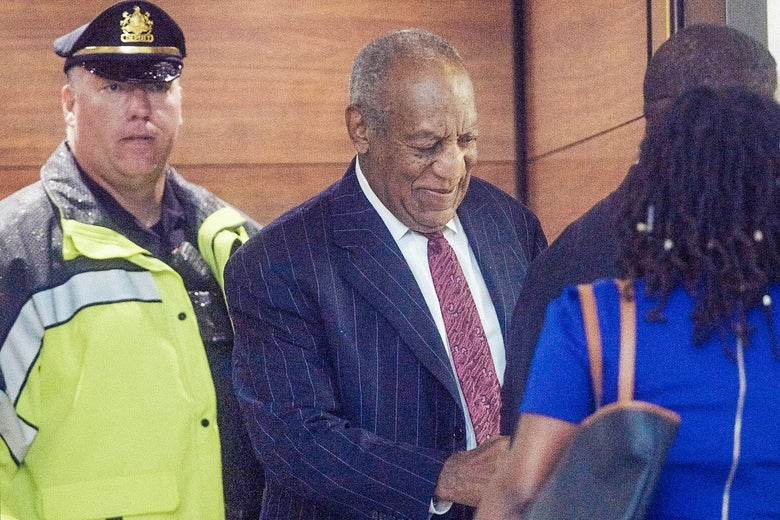 Bill Cosby smiles as he steps out of an elevator at the courthouse wearing a suit.