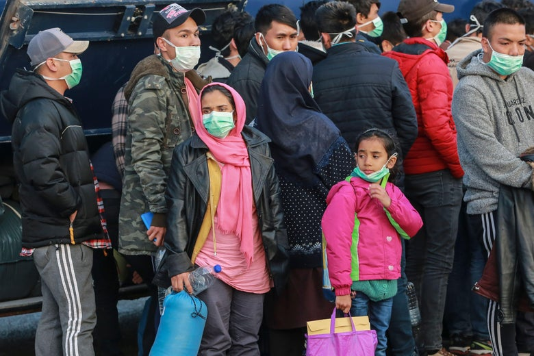 Refugees stand in line wearing masks.