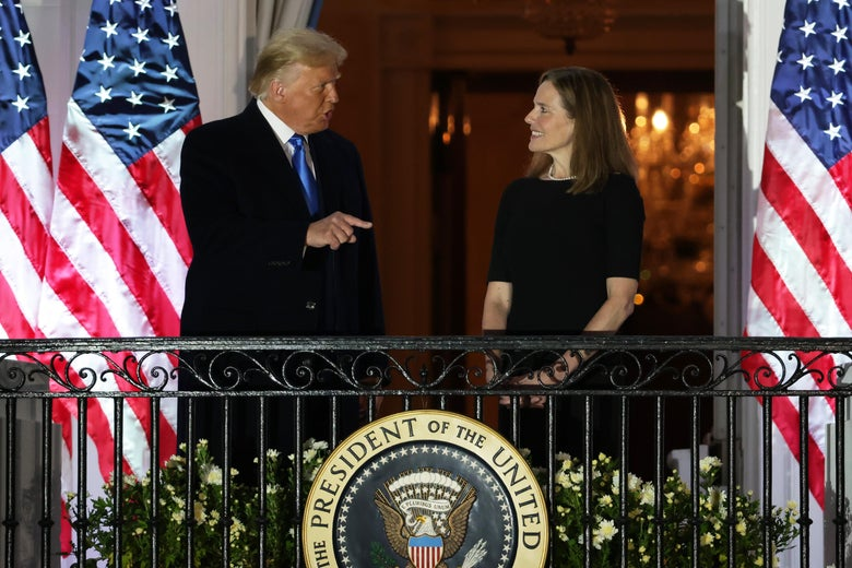 Donald Trump points as he speaks with Amy Coney Barrett on a White House balcony.