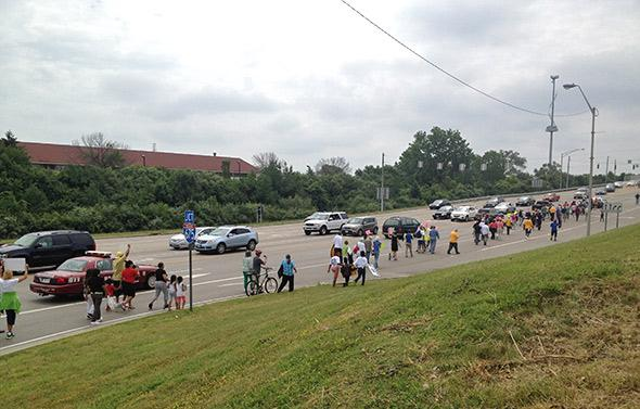 Dayton residents march along a highway to protest the lack of bus service to area malls in June 2013.
