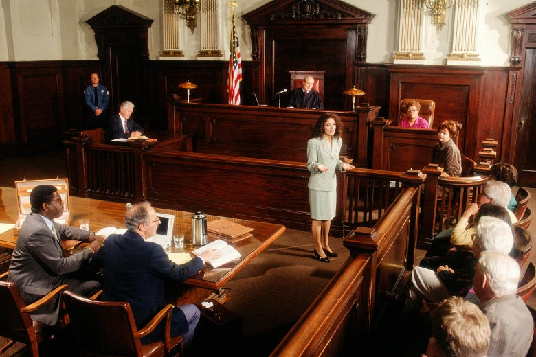 A female prosecutor stands and speaks to the jury in a courtroom