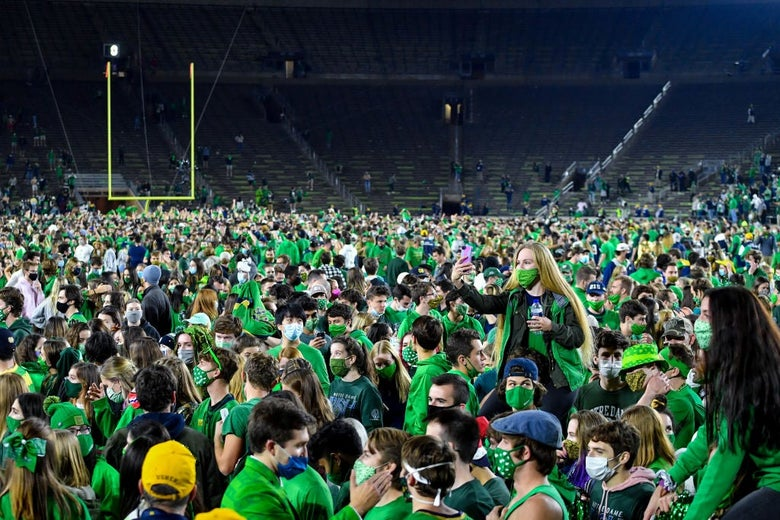 Hundreds (possibly thousands) of young fans wearing green, most wearing masks, are seen against a backdrop of empty bleachers.