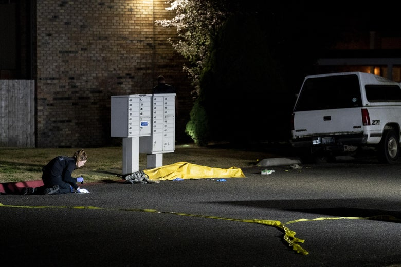 An investigator, kneeling, inspects something on the ground next to the dead body, which is covered by a tarp underneath a mailbox