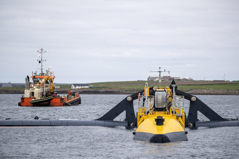 A boat and a tidal generator sit in the water with land in the background.