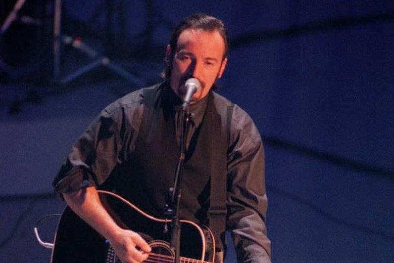 Bruce Springsteen plays guitar and sings onstage.