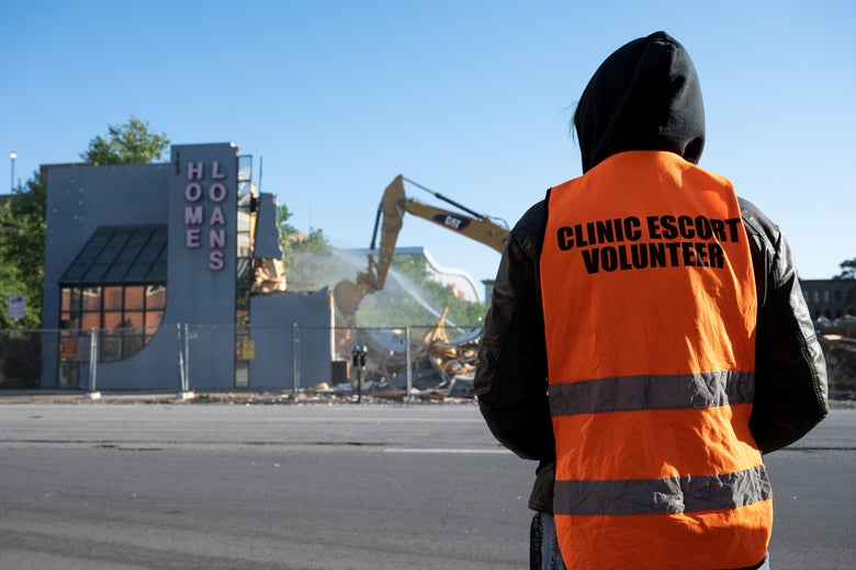 """A person in a hooded sweatshirt and a bright-orange vest that says """"Clinic escort volunteer"""" is seen from behind as they look out on a construction site across the street."""