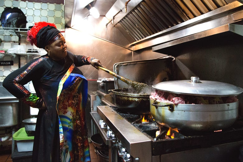 Fanta Fofana stirs a pot of cassava leaf stew in the kitchen of her restaurant, Le Mandingue.