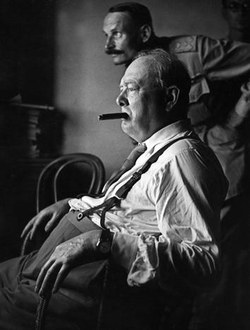 British Prime Minister Sir Winston Churchill, stripped to shirt sleeves and smoking a cigar, looks at enemy positions from a fortified forward position in Italy, 1944.