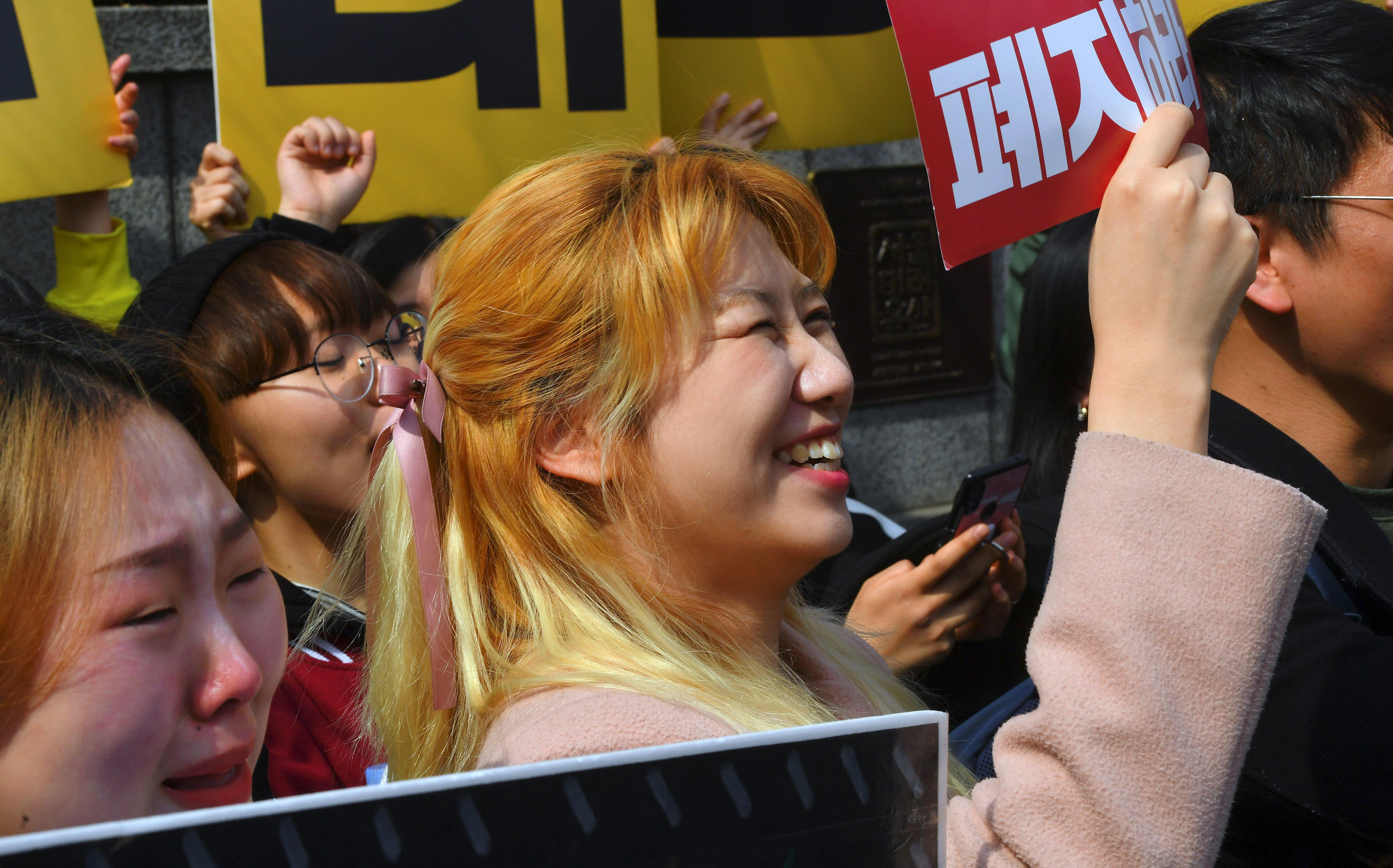 South Korean women hold up banners to protest anti-abortion legislation.