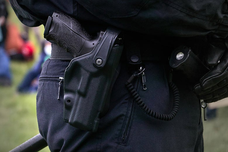 A pistol in the holster of a uniformed police officer wearing leather gloves.