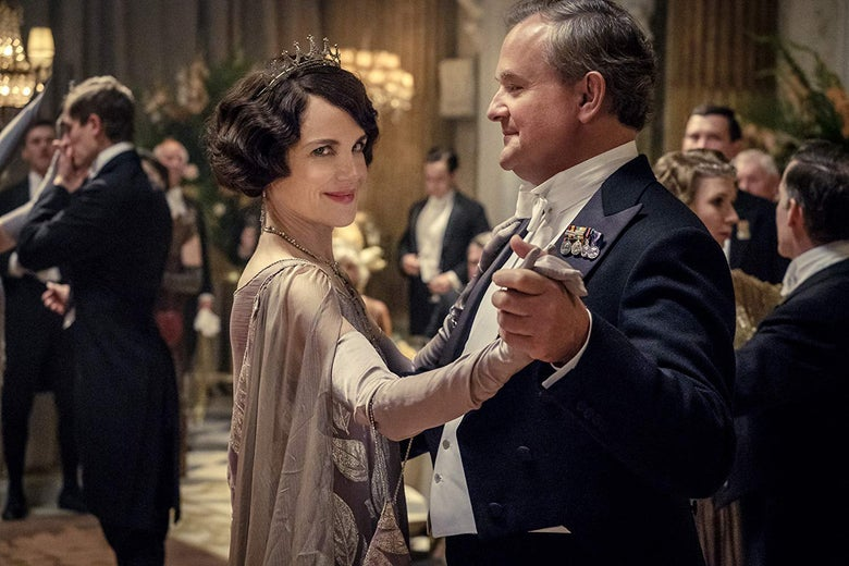 Elizabeth McGovern gives the camera a sly smile while dancing with Hugh Bonneville in a still from Downton Abbey.