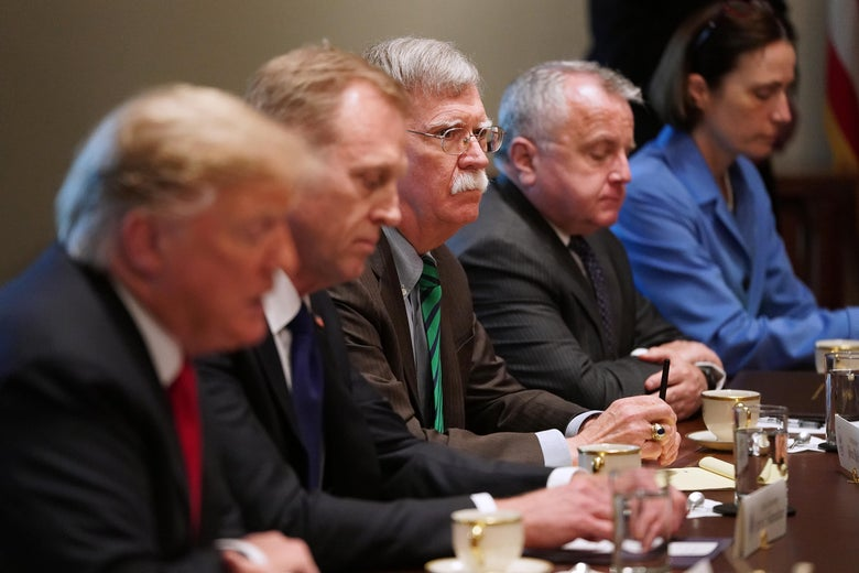 John Bolton seen in focus next to Trump in the foreground in the Cabinet Room.