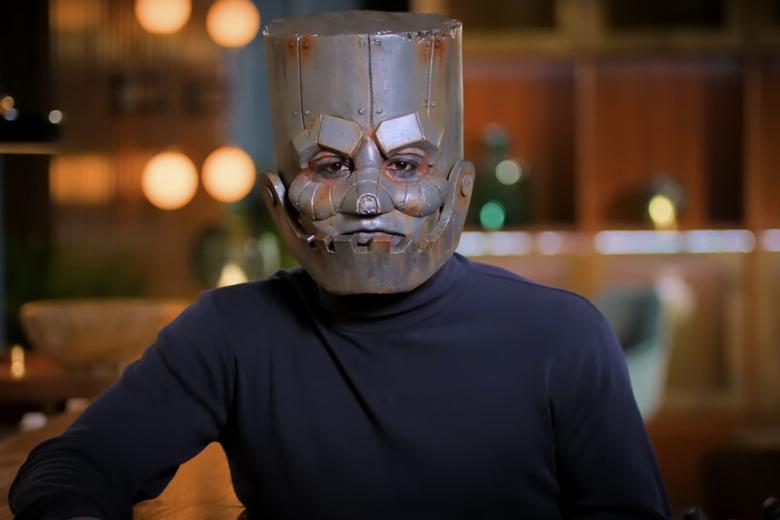 Man in navy turtleneck wearing a robot mask.