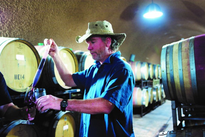 Alex MacGregor using a wine thief, a glass tube that acts like a baster, to put drawn wine into a glass for tasting.