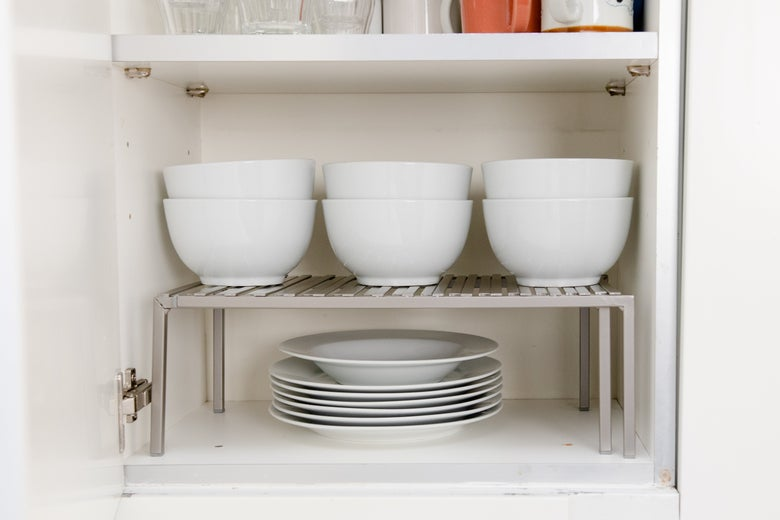 Shelf riser with dishes on it.