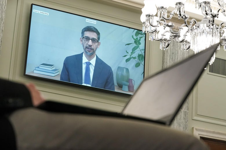 A person with a laptop is in the foreground while Sundar Pichai is on a large screen on the wall.