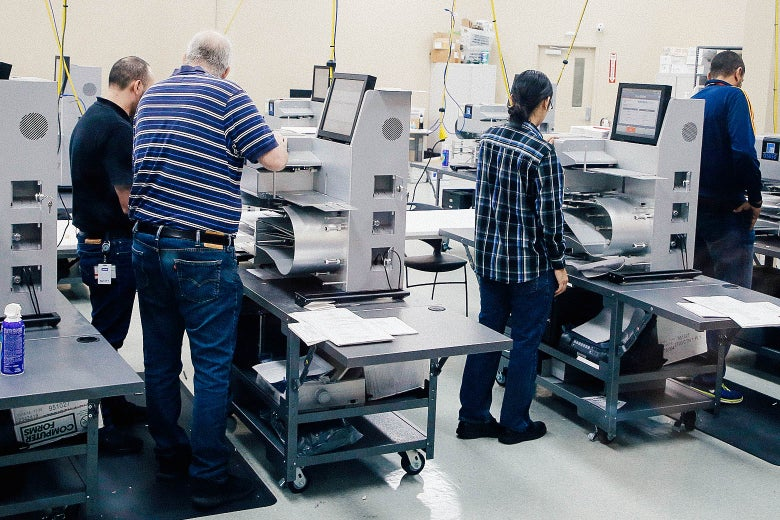 Elections officials work at machines.
