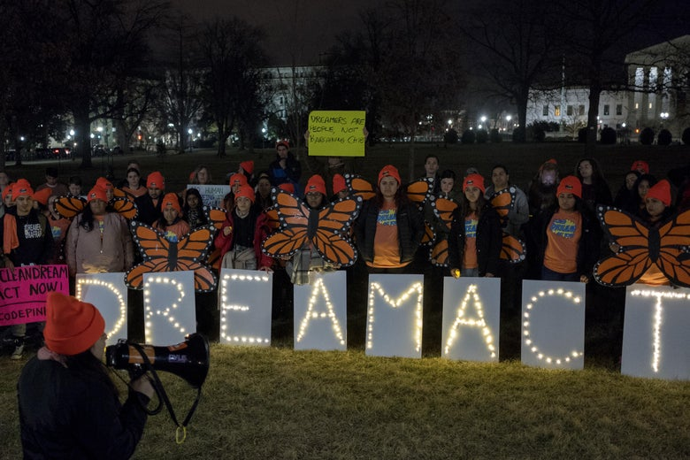 Protesters stand behind signs with letters lit up spelling D-R-E-A-M A-C-T.