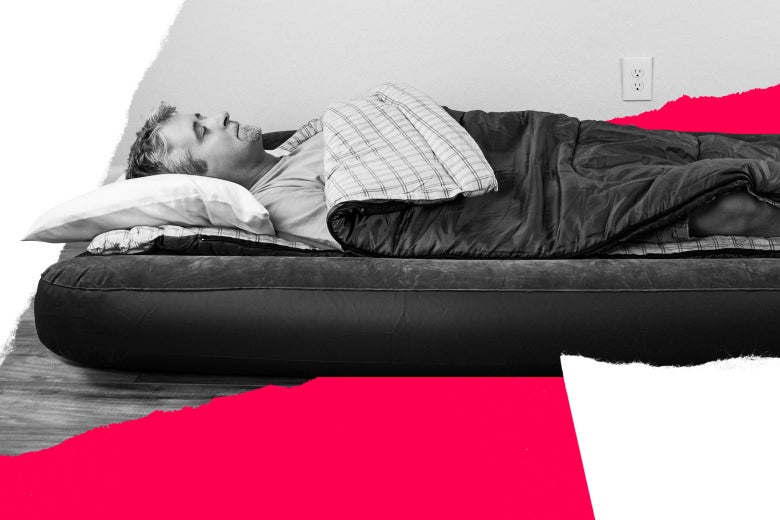 A man lies with his eyes closed on an air mattress in a sleeping bag.