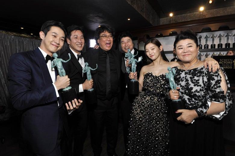 Actors Choi Woo-shik,  Lee Sun Gyun, Bong Joon-ho, Song Kang Ho, Park So-dam, and Jeong-eun Lee, dressed in formal wear and smiling broadly, hold their SAG Awards.