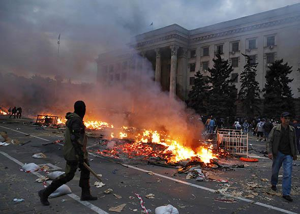 A protester walks past a burning pro-Russian tent camp near the trade union building in Odessa May 2, 2014.