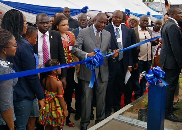 Governor Amaechi cuts the ribbon at the unveiling ceremony for a new water purification plant funded by Shell, flanked by government officials and representatives of Shell Nigeria.