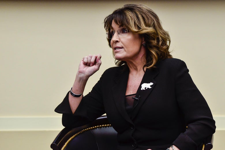 Sarah Palin sits in a chair, speaking. She wears a pin with a bear on it.