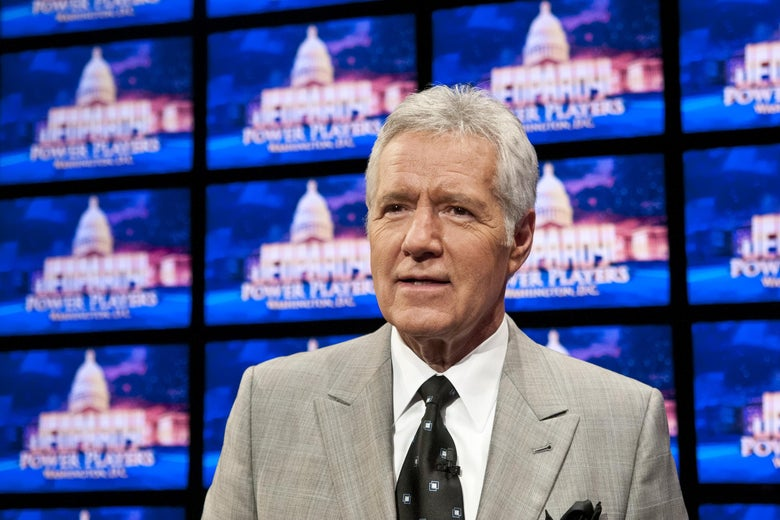 Alex Trebek stands in front of a wall of screens, all with the Jeopardy! logo.