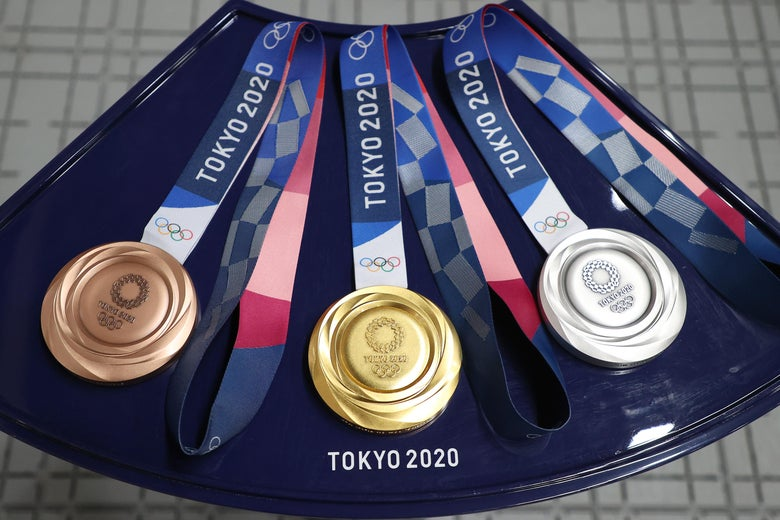 L-R: a bronze, gold, and silver medal from the Tokyo Olympics sitting on a platter.