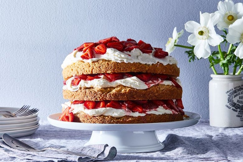 A three-layer vanilla cake doused in whipped cream and fresh strawberries sits on a white cake stand.