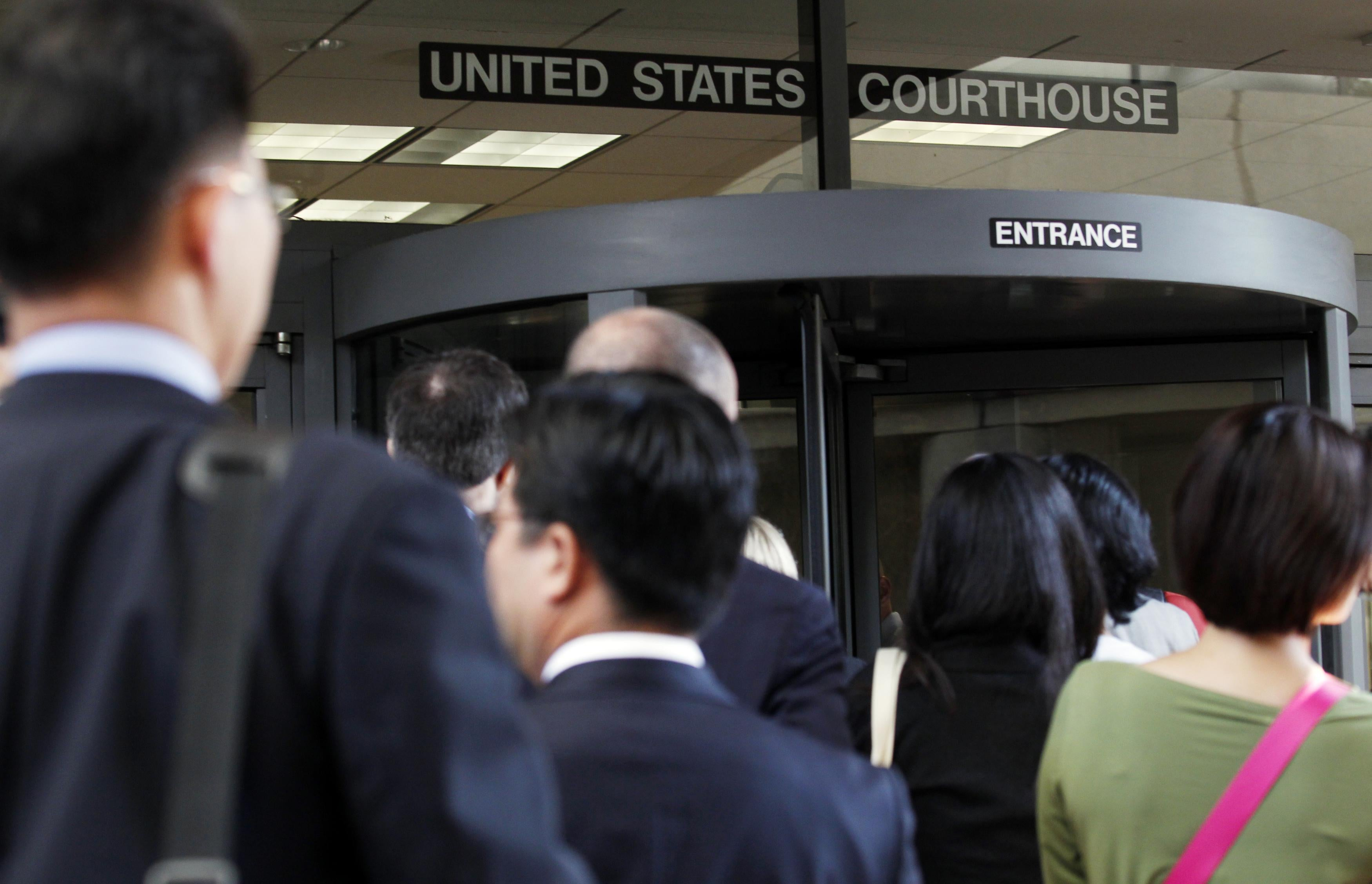 Individuals line up to enter the Robert F. Peckham United States Courthouse Building to watch Apple and Samsung face each other in federal district court for a patent infringement case on July 30, 2012 in San Jose, California.